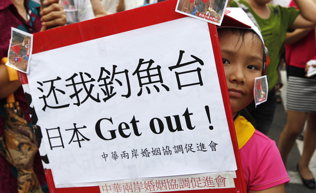 A girl holding a placard takes part in an anti-Japan protest in Taipei