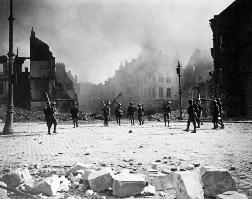 William Rider-Rider_ A group of Canadian soldiers strung out in the streets of Cambrai against its still burning buildings. Imperial War Museum, CO3373.