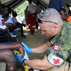 Canadian army medic Cpl. Champagae Leblanc treats an injured Haitian boy at a Canadian-run medical treatment camp near L?og?ne, Haiti, Jan. 25, 2010. Haiti was devastated by a 7.0-magnitude earthquake Jan. 12, 2010. (U.S. Air Force photo by Tech. Sgt. Prentice Colter/Released)