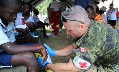 Canadian army medic Cpl. Champagae Leblanc treats an injured Haitian boy at a Canadian-run medical treatment camp near L?og?ne, Haiti, Jan. 25, 2010. Haiti was devastated by a 7.0-magnitude earthquake Jan. 12, 2010. (U.S. Air Force photo by Tech. Sgt. Prentice Colter/Released)