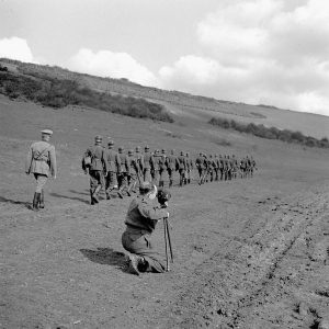 Sergeant Alan Grayston of the Canadian Army Film and Photo Unit filming a  Canadian demonstration of German infantry tactics, Polegate, England, 28  March 1943. Photography by Lieut. Jack H. Smith/ Dept. of National Defence/  Library and Archives Canada / MIKAN 3210377.